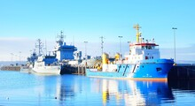Moored Tugboat And Military Ships On A Pier In Kiel, Germany. Transportation, Nautical Vessel, Global Communications And Security, Logistics