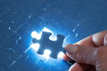 The Missing Piece Of The Puzzle With Light, The Concept Of Completing A Big Job, The Final Of The Project, The Successful Solution Of Business Problems. The Hand Puts The Last Piece Of The Jigsaw