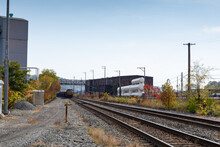 Train Coming Down A Track Running Alongside Industrial Buildings In A Rural Area, Fall Season With Autumn Leaves, Horizontal Aspect