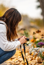 A Young Girl Squatting And Taking Pictures With A Camera In The Autumn Garden.