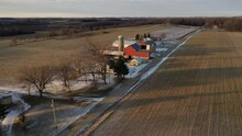Establishing Shot Of Midwestern Countryside In Spring Winter Season.  Aerial View Of Rustic Road, Farms, Farm Houses, Agricultural Fields. Sunny, Sunlight At Sunset. Wisconsin, United States