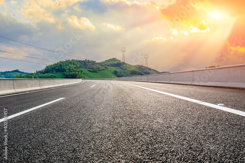 Fototapeta Asphalt road and mountain at sunset.Road and mountain background. obraz