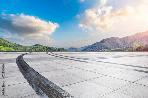 Empty square floor and green mountain background.