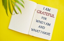 I Am Grateful For What I Am And What I Have Inspirational Handwriting On Notebook. Concept Of Things I Am Thankful For, Yellow Background