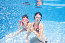 Family Swims In Pool Underwater, Happy Active Mother And Child Have Fun Under Water, Fitness And Sport With Kid On Summer Vacation On Resort