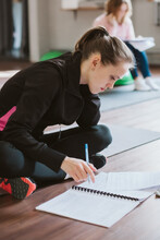 A Young Girl At A Master Class Or Training. A White Caucasian Girl Sits On The Floor And Writes Down Information In A Notebook During Training. Fittness Convention Of Trainers. Lifestyle Photos