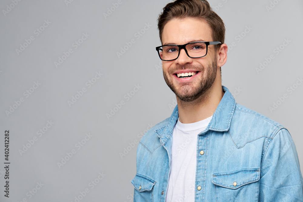 Fototapeta Portrait of young handsome caucasian man in jeans shirt over light background