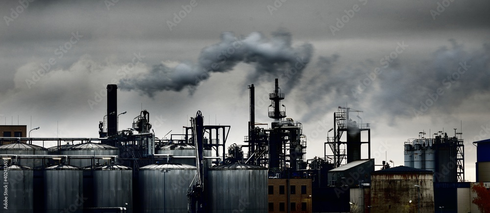 Fototapeta Chemical factory on a hazy day; silos, factory pipe, smoke. Dark panoramic urban cityscape. Industry, business, technology. fuel and power generation, ecological issues, environmental damage