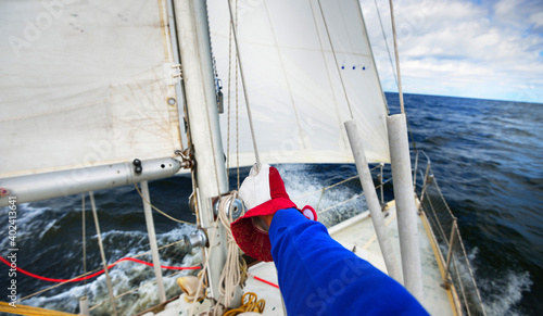 Fototapety, obrazy: View of a yacht in strong wind with a sailors hand holding a cab. Transportation, nautical vessel, cruise, sport, regatta, recreation, leisure activity, yachting, work, sailing team