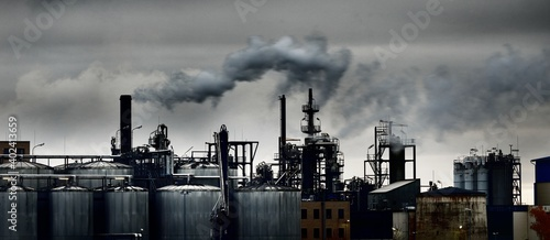 Chemical factory on a hazy day; silos, factory pipe, smoke. Dark panoramic urban cityscape. Industry, business, technology. fuel and power generation, ecological issues, environmental damage - fototapety na wymiar