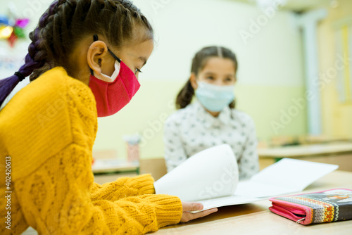 Tablou Canvas Girls in protective masks sit at their desks in the lesson and read the textbook