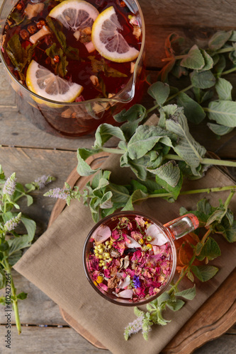Jug and cup with floral tea on wooden background