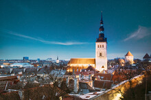 Tallinn, Estonia. Night Starry Sky Above Traditional Old Architecture Skyline In Old Town. St. Nicholas Church - Niguliste Kirik In Winter Evening Night. Famous Landmark. Altered Sky With Stars