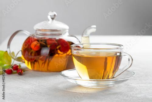 Fototapeta Fresh rosehip berries are brewed in a transparent teapot obraz