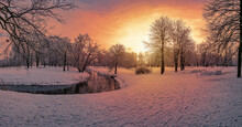 Panoramic View Of Sunset Over Park With Small Canal With Ducks And Covered In Snow Trees
