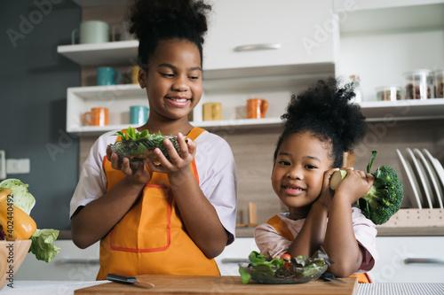 Happy sister black skin with salad on plate in kitchen Fototapeta
