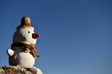 Funny Snowman Looking Out Into The Blue Sky, Snowman Made Ob Ceramic With Hut, Orange Nose, Scarf