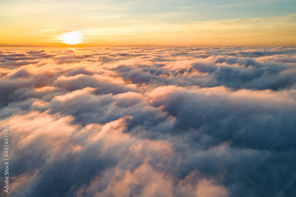 Obraz Aerial view of bright yellow sunset over white dense clouds with blue sky overhead. fototapeta, plakat