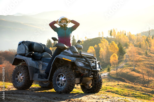Obraz Happy active female driver in protective helmet enjoying extreme riding on ATV quad motorbike in fall mountains at sunset. - fototapety do salonu