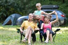 Happy Young Family Parents And Their Kids Resting Together At Camping Site In Summer.