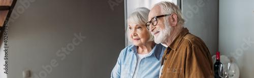 Fotografía smiling senior couple looking away indoors, banner