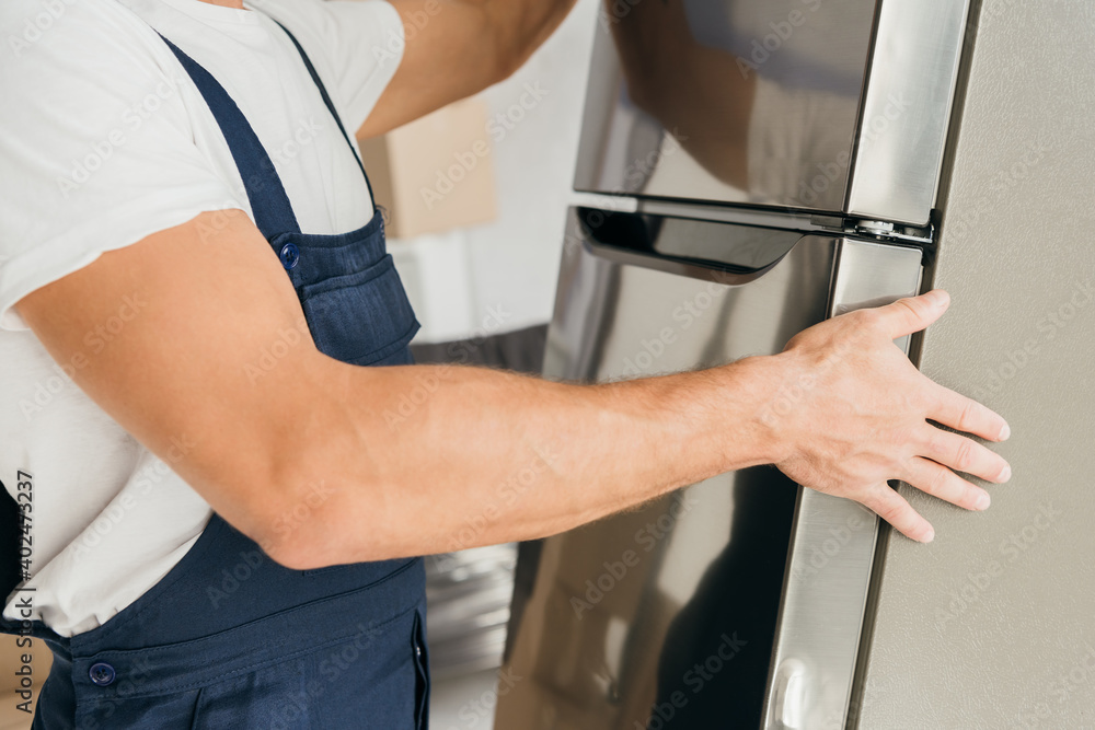 Obraz cropped view of strong workman moving fridge in apartment fototapeta, plakat