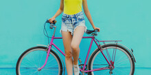 Close Up Of Beautiful Woman Model In Shorts With Bicycle Posing On A Blue Background