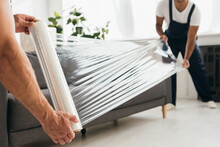 Cropped View Of Movers Holding Stretch Film Roll Near Sofa