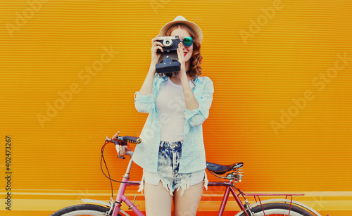Canvas Print Happy young woman with film camera and bicycle on an orange background