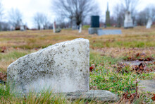 The Bottom Of An Old, Broken Grave Marker. The Stone Is Made Of Marble And Broken. Low Angle Closeup. Other Graves In The Background, Overcast Sky.