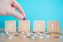 COST; 4個の積み木ブロックで作ったCOSTの概念とたくさんのコイン(お金)