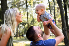 Photography Of Family With One Child In Nature. Dad Is Holding Baby In Air, While Mom Is Standing Behind Him And Coo To Baby. Boy Is Smiling Back. Weekend Family Time.