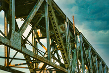 A Close Up Of The Girders Under A Railroad Trestle With An Dark Sky Above.