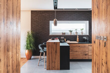 Black Brick Wall In Elegant Kitchen With Wooden Island And Stylish Chairs