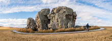 Big Rock Erratic Okotoks Tourist Destination Giant Boulder In The Prairies Landscape At Sunset Golden Hour. Person Walking On Pathway At Point Of Interest Panorama