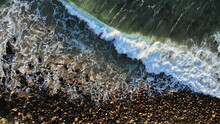 A Wave Crashes Into A Rocky Shore Along A Point Break Popular With Surfers