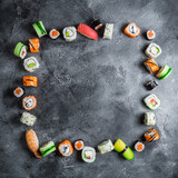 Fototapeta Kawa jest smaczna - Sushi frame on dark background. Sushi rolls, nigiri, raw salmon steak, rice, and avocado. Flat lay