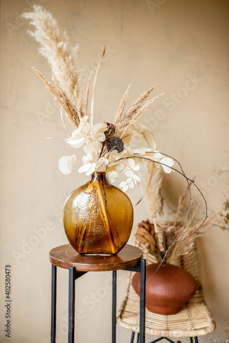 Composition of dried flowers and herbs in vases on a beige wall background