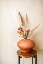 Composition Of Dried Flowers In A Clay Vase On A Beige Wall Background. Bouquet Of Pampas Grass, Cortaderia, Banksia, Proteaceae, Gomphrena