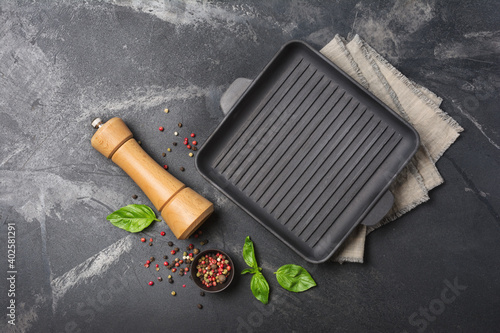 Fototapeta Grill pan with bright spices, basil leaves and pepper mill for tasty cooking obraz