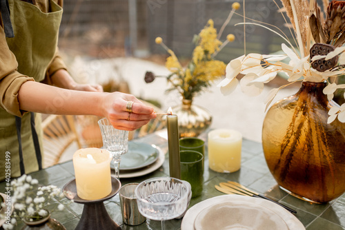 Fototapeta Young female lighting candles while decorating dinning table in natural Boho style in green tones outdoors obraz