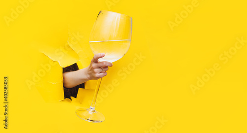 Fotografie, Obraz A right woman's hand emerges through a torn hole in yellow paper with a large glass with vermouth, water or vodka