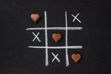 Chocolate Hearts And Grid Of Tic-tac-toe On Black Grainy Cardboard. Love Game Concept. Flat Lay