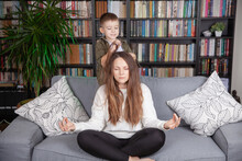 Mom Try To Keep Calm. Young Woman Meditating, While Annoyed About Noisy Active Kid Playing At Home.