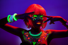 Front Portrait Of A Woman With Artistic Colorful Makeup And Orange Wig, With Closed Eyes, Isolated Violet Background.