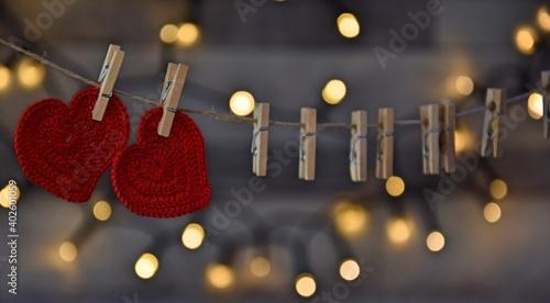 Czerwone serduszka na sznurze przypięte spinaczami vintage background Valentine's day, romantyczne tło