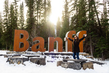 Young Woman Posing In Front Of The Banff 3D Giant Letters Sign At The Entrance Of Banff, Canada