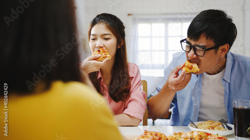 Obraz Happy young friends group having lunch at home. Asia family party eating pizza food and laughing enjoying meal while sitting at dining table together at house. Celebration holiday and togetherness. - fototapety do salonu