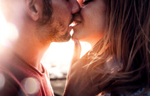 Romantic Couple In Love Kissing At Sunset - Boyfriend And Girlfriend Having A Romance Kiss Outdoor - Warm Filter