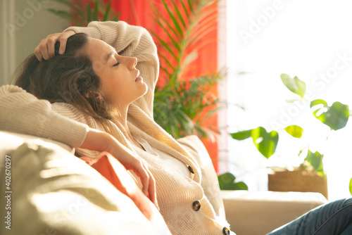 Obraz Depressed young woman sitting on sofa at home - fototapety do salonu